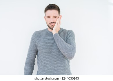 Young handsome man wearing casual sweater over isolated background touching mouth with hand with painful expression because of toothache or dental illness on teeth. Dentist concept.