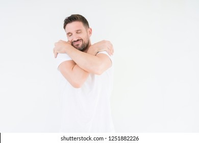 Young handsome man wearing casual white t-shirt over isolated background Hugging oneself happy and positive, smiling confident. Self love and self care