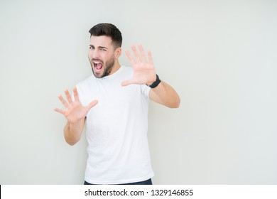 Young handsome man wearing casual white t-shirt over isolated background afraid and terrified with fear expression stop gesture with hands, shouting in shock. Panic concept.