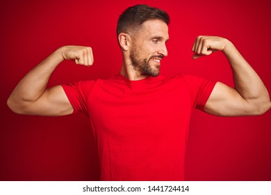 Young handsome man wearing casual t-shirt over red isolated background showing arms muscles smiling proud. Fitness concept.