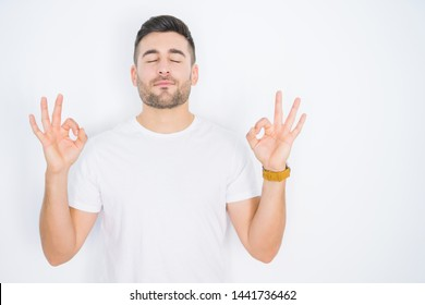 Young handsome man wearing casual white t-shirt over white isolated background relax and smiling with eyes closed doing meditation gesture with fingers. Yoga concept.