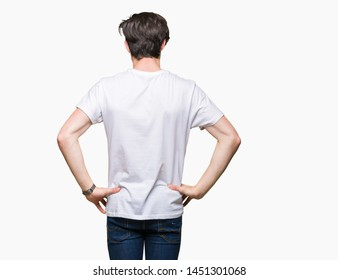 Young handsome man wearing casual white t-shirt over isolated background standing backwards looking away with arms on body