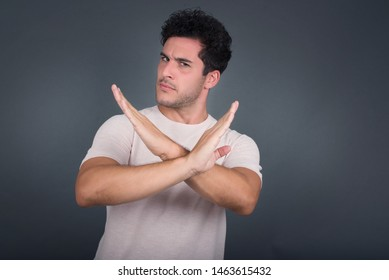 Young handsome man wearing casual clothes standing over isolated background. Has rejection angry expression crossing hands doing refusal negative sign.