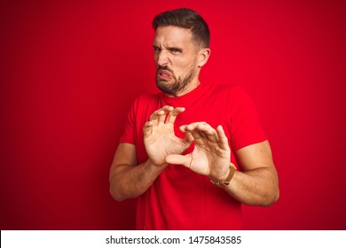 Young handsome man wearing casual t-shirt over red isolated background disgusted expression, displeased and fearful doing disgust face because aversion reaction. With hands raised. Annoying concept.