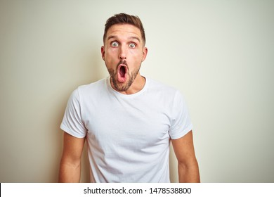 Young handsome man wearing casual white t-shirt over isolated background afraid and shocked with surprise expression, fear and excited face.