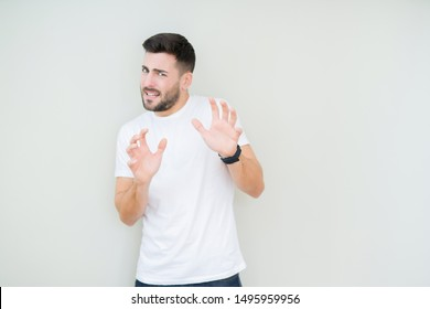 Young handsome man wearing casual white t-shirt over isolated background disgusted expression, displeased and fearful doing disgust face because aversion reaction. With hands raised. Annoying concept.