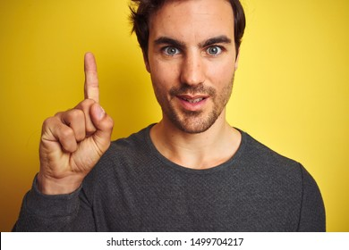 Young handsome man wearing casual sweater standing over isolated yellow background surprised with an idea or question pointing finger with happy face, number one