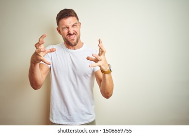 Young handsome man wearing casual white t-shirt over isolated background Shouting frustrated with rage, hands trying to strangle, yelling mad