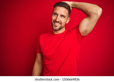Young handsome man wearing casual t-shirt over red isolated background smiling confident touching hair with hand up gesture, posing attractive and fashionable