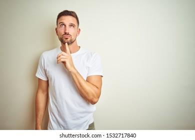 Young handsome man wearing casual white t-shirt over isolated background Thinking concentrated about doubt with finger on chin and looking up wondering