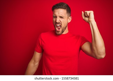 Young handsome man wearing casual t-shirt over red isolated background Dancing happy and cheerful, smiling moving casual and confident listening to music