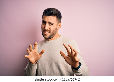 Young handsome man wearing casual sweater standing over isolated pink background disgusted expression, displeased and fearful doing disgust face because aversion reaction. With hands raised
