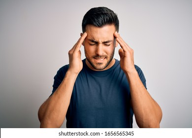 Young handsome man wearing casual t-shirt standing over isolated white background with hand on head for pain in head because stress. Suffering migraine.