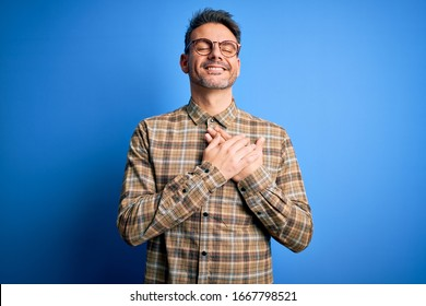 Young handsome man wearing casual shirt and glasses standing over blue background smiling with hands on chest with closed eyes and grateful gesture on face. Health concept.