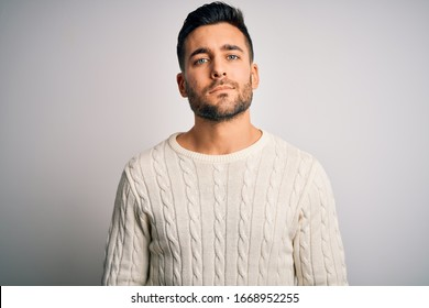 Young handsome man wearing casual sweater standing over isolated white background Relaxed with serious expression on face. Simple and natural looking at the camera.