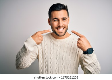 Young handsome man wearing casual sweater standing over isolated white background smiling cheerful showing and pointing with fingers teeth and mouth. Dental health concept.