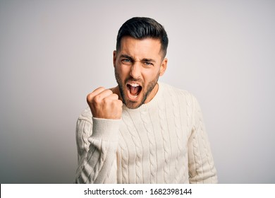 Young handsome man wearing casual sweater standing over isolated white background angry and mad raising fist frustrated and furious while shouting with anger. Rage and aggressive concept.