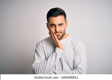 Young handsome man wearing casual t-shirt standing over isolated white background thinking looking tired and bored with depression problems with crossed arms.