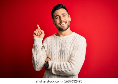 Young handsome man wearing casual white sweater standing over isolated red background with a big smile on face, pointing with hand and finger to the side looking at the camera.