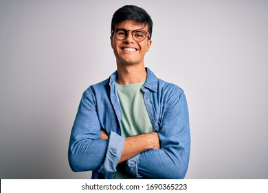 Young handsome man wearing casual shirt and glasses over isolated white background happy face smiling with crossed arms looking at the camera. Positive person.