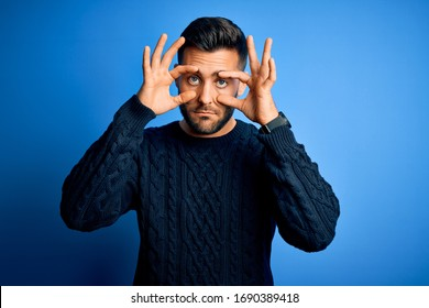 Young handsome man wearing casual sweater standing over isolated blue background Trying to open eyes with fingers, sleepy and tired for morning fatigue