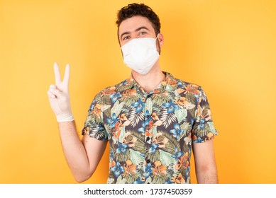 Young handsome man wearing casual hawaiian shirt with medical mask and gloves standing over isolated yellow background smiling with happy face winking at the camera doing victory sign. Number two.