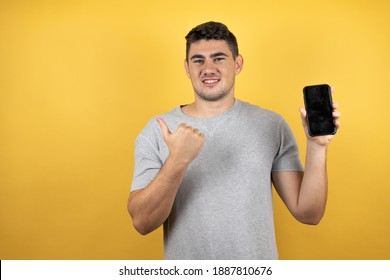 Young handsome man wearing a casual t-shirt over isolated yellow background smiling, pointing to the copy space and holding a phone with the other hand