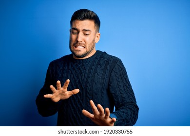 Young handsome man wearing casual sweater standing over isolated blue background disgusted expression, displeased and fearful doing disgust face because aversion reaction.