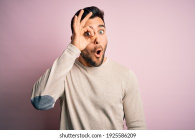 Young handsome man wearing casual sweater standing over isolated pink background doing ok gesture shocked with surprised face, eye looking through fingers. Unbelieving expression.
