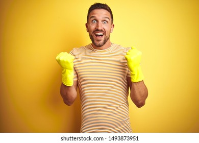 Young handsome man wearing cleaning gloves for housework over isolated yellow background screaming proud and celebrating victory and success very excited, cheering emotion