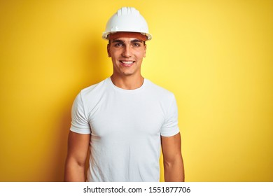 Young handsome man wearing construction helmet over yellow isolated background with a happy and cool smile on face. Lucky person.