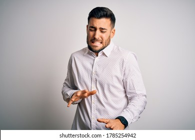 Young handsome man wearing elegant shirt standing over isolated white background disgusted expression, displeased and fearful doing disgust face because aversion reaction.