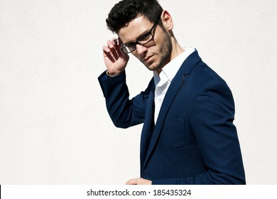 Young handsome man wearing fashion eyeglasses against neutral background with lots of copy space