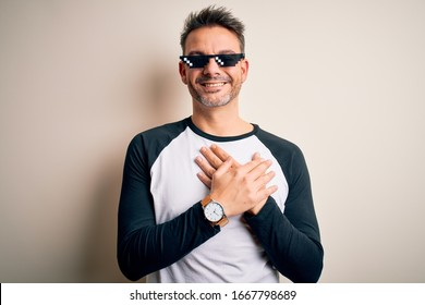Young handsome man wearing funny thug life sunglasses meme over white background smiling with hands on chest with closed eyes and grateful gesture on face. Health concept.