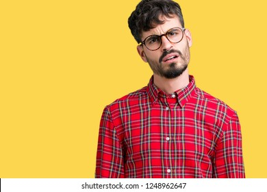 Young handsome man wearing glasses over isolated background In shock face, looking skeptical and sarcastic, surprised with open mouth