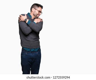 Young handsome man wearing glasses over isolated background Hugging oneself happy and positive, smiling confident. Self love and self care