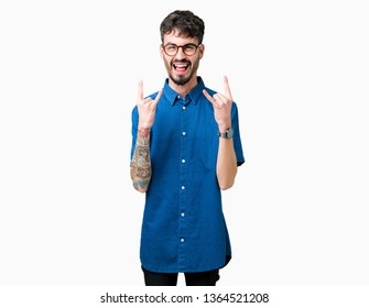 Young handsome man wearing glasses over isolated background shouting with crazy expression doing rock symbol with hands up. Music star. Heavy concept.