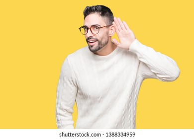 Young handsome man wearing glasses over isolated background smiling with hand over ear listening an hearing to rumor or gossip. Deafness concept.