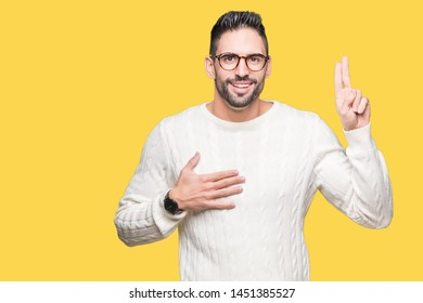 Young handsome man wearing glasses over isolated background Swearing with hand on chest and fingers, making a loyalty promise oath
