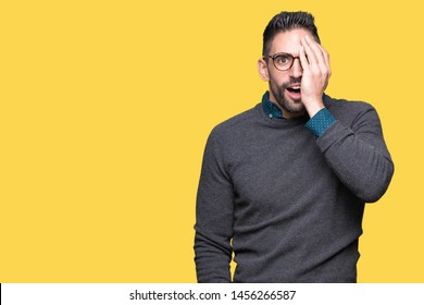Young handsome man wearing glasses over isolated background covering one eye with hand with confident smile on face and surprise emotion.