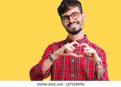 Young handsome man wearing glasses over isolated background smiling in love showing heart symbol and shape with hands. Romantic concept.