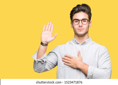 Young handsome man wearing glasses over isolated background Swearing with hand on chest and open palm, making a loyalty promise oath