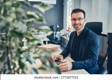 Young handsome man wearing glasses in the blue suit working at the desk on the laptop