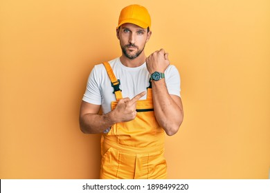 Young handsome man wearing handyman uniform over yellow background in hurry pointing to watch time, impatience, looking at the camera with relaxed expression