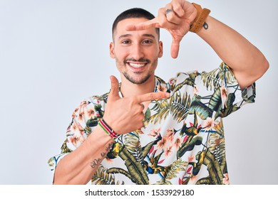 Young handsome man wearing Hawaiian summer shirt over isolated background smiling making frame with hands and fingers with happy face. Creativity and photography concept.