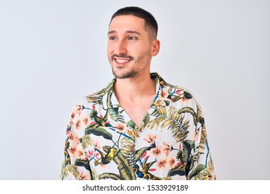 Young handsome man wearing Hawaiian summer shirt over isolated background looking away to side with smile on face, natural expression. Laughing confident.