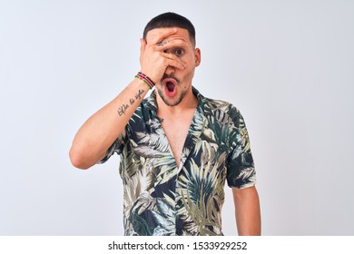 Young handsome man wearing Hawaiian summer shirt over isolated background peeking in shock covering face and eyes with hand, looking through fingers with embarrassed expression.