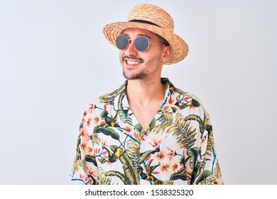 Young handsome man wearing Hawaiian shirt and summer hat over isolated background looking away to side with smile on face, natural expression. Laughing confident.