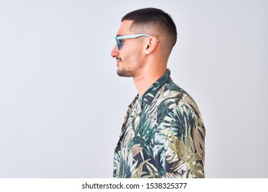 Young handsome man wearing Hawaiian sumer shirt and blue sunglasses over isolated background looking to side, relax profile pose with natural face with confident smile.