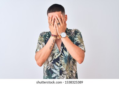 Young handsome man wearing Hawaiian summer shirt over isolated background with sad expression covering face with hands while crying. Depression concept.